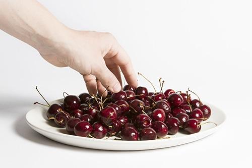 Persona comiendo cerezas